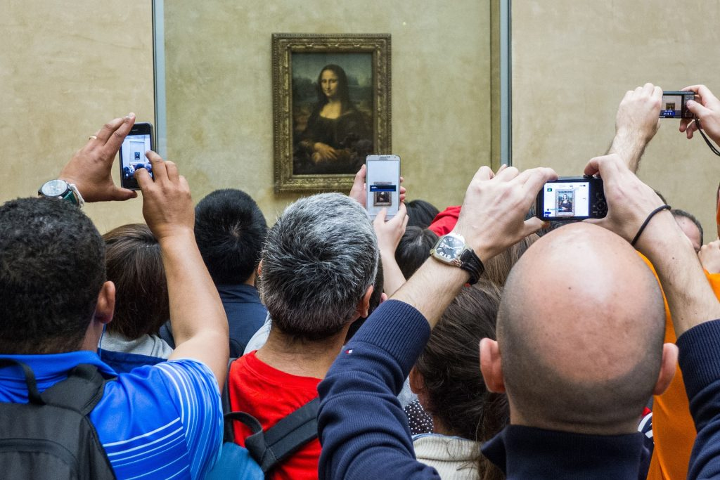 Crowds gather around Mona Lisa. Overtourism in Paris.